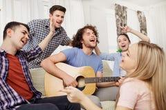 En grupp av vänner med sånger för en gitarrallsång på ett parti inomhus royaltyfri bild