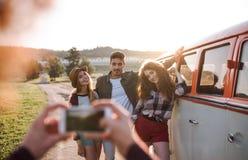 En grupp av vänner med smartphonen på en roadtrip till och med bygd som tar fotoet fotografering för bildbyråer