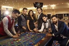 En grupp av vänner på kasinorouletttabellen fotografering för bildbyråer