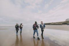 En grupp av vänner promenerar en vinterstrand arkivfoto