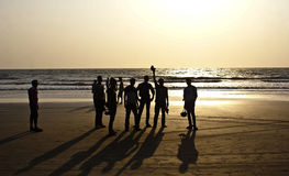 En grupp av vänner silhouetted på den Arambol stranden, norr Goa Royaltyfria Bilder