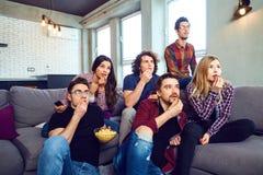 En grupp av vänner som äter wathing tv för pizza i rummet arkivfoton