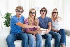 En grupp av vänner som håller ögonen på en läskig film 3d Arkivfoto