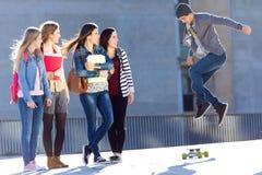 En grupp av vänner som har gyckel med skridskon i gatan Arkivbild