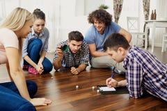En grupp av vänner spelar brädelekar på golvet inomhus royaltyfria foton