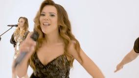 En grupp av yrkesmässiga skådespelare som dansar på en vit bakgrund Flickasångaren i den svarta klänningen Två unga män i svart stock video