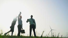 En grupp människor i affärsdräkter ger höjdpunkt fem på bakgrund för vindgeneratorer stock video