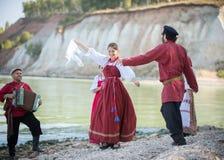 En grupp människor i härliga ryska folk beklär dansen mot vattnet, dans i mitten av en ung flicka arkivbild
