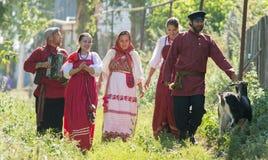 En grupp människor i ryska nationella dräkter går till och med byn, förbi dem är en get arkivfoto