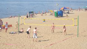 En grupp människor, män och kvinnor som spelar strandvolleyboll arkivfilmer