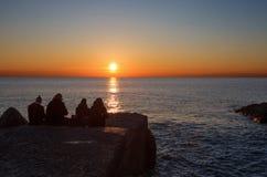 En grupp människor sitter ner se solnedgång framme av havet arkivfoto