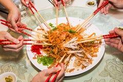 En grupp människor som blandar och kastar den Yee Sang maträtten med kotlett, klibbar Yee Sang är en populär läckerhet som tas un