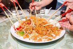 En grupp människor som blandar och kastar den Yee Sang maträtten med kotlett, klibbar Yee Sang är en populär läckerhet som tas un royaltyfri foto