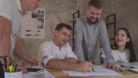 En grupp som är lycklig av kontorsanställda, arbetar sent, diskuterar utkast och gör anmärkningar arkivfilmer