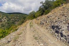 En grusväg på en brant berglutning royaltyfria bilder