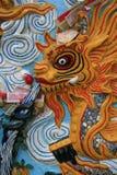 En gul drake skulpterades på en vägg i borggården av en buddistisk tempel i Hanoi (Vietnam) Fotografering för Bildbyråer