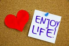En gul klibbig anmärkningshandstil, överskrift, inskrift att tycka om liv, motivational livsstilpåminnelser mot svart ext på a royaltyfri bild