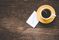 En gul kopp kaffemorgon på den gamla trätabellen Arkivfoto