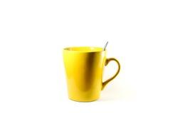 En gul kopp på vit bakgrund Fotografering för Bildbyråer