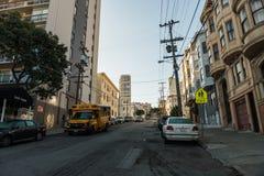 En gul skolbuss väntar i en i stadens centrum gata i San Francisco, Kalifornien, USA fotografering för bildbyråer