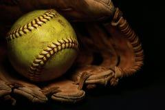En gul softball i ett gammalt, brunt, läderhandske arkivfoton