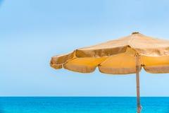 En gul solslags solskydd mot horisont för blått vatten och himmelmed kopieringsutrymme Royaltyfria Foton