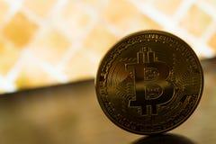 En guld- bitcoin på gul backround Arkivbilder