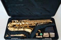 En guld-/mässingsalt- saxofon på vit bakgrund med pärlatangenter - lade ut i fall att med tillbehör arkivbilder