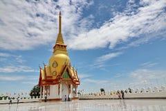 En guld- pagod står ut från den blåa himlen i central region av Thailand Royaltyfri Bild