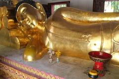 En guld- staty av Buddha upptar en av korridorerna av en tempel (Thailand) Arkivbilder