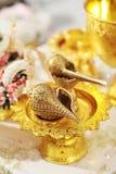 En guld- trumpetsnäckauppsättning och blommagirlander för thailändskt vatten som häller gifta sig c Royaltyfria Foton