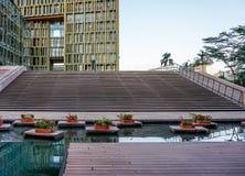 En guld- yttersida av en modern byggnad med ett utomhus- damm och blommor Royaltyfri Fotografi