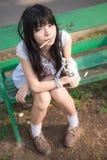 En gullig asiatisk thailändsk flicka sitter på bänken med en pinne i H Arkivbild