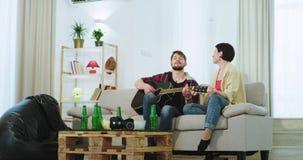 En gullig dam för två vänner med kort hår och grabben i en vardagsrum har en bra tid tillsammans dem som spelar på en gitarr och arkivfilmer