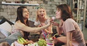 En gullig damtonåring i pyjamas har ett sött parti på sängen dem som äter sötsaker och tycker om tidutgifter stock video