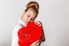 En gullig flicka som packar upp den röd hjärta formade gåvan Fira helgonvalintines dag royaltyfri fotografi