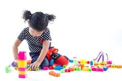 En gullig flicka som spelar kvarterleksaken på vit bakgrund Royaltyfria Bilder