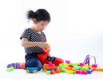 En gullig flicka som spelar kvarterleksaken på vit bakgrund Royaltyfri Foto