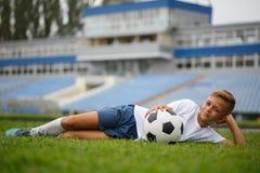 En gullig grabb med en fotbollboll som lägger på ett grönt gräs och på en stadionbakgrund En fotbollsspelare i det fria Royaltyfri Foto