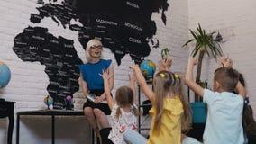 En gullig kvinnaläraregyckel ler på barnen under kursen och kontrollerar kunskap av hans elever som lyfter deras stock video