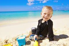 Pys som leker i sanden på strand Arkivfoton