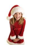 En gullig liten flicka i en Santa Claus Hat och en julklänning Arkivfoton