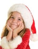 En gullig liten flicka i en Santa Claus Hat och en klänning Royaltyfri Foto