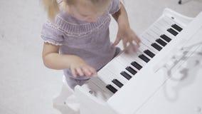 En gullig liten flicka sitter på stilfulla barns piano och spelar musik stock video
