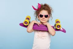 En gullig liten lockig flicka, i solglasögon som rymmer i studio med skateboarden i händer som isoleras på en blå bakgrund fotografering för bildbyråer