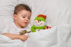 En gullig litet barnpojke sover på vit linne med hans favorit- leksaksnögubbe royaltyfri bild