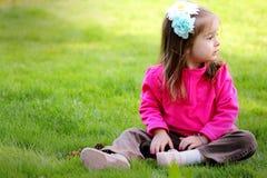 Den söta litet barn sitter i gård arkivbilder
