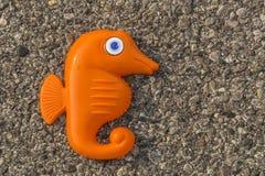 En gullig plast- Seahorse på en grov bakgrund Arkivfoto
