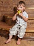 En gullig pojke med ett äpple. Arkivbilder