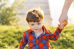 En gullig pojke som har den roliga yttersidan i landet i sommar på solnedgången en pojke som spelar med gula maskrosor i trädgård Arkivfoto